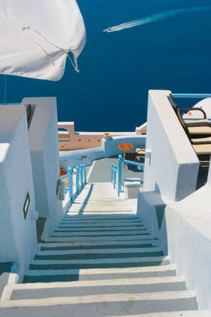 White street with long staircase and traditional architecture on island of Santorini in Fira, Greece. Aegean sea in the background. photo