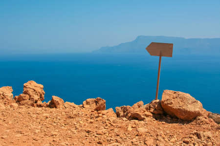 Beautiful Mediterranean sea near the damaged road, which leads to Gramvoussa beach on island of Crete in Greece. Empty signpost in a stone covered with orange dust. photo
