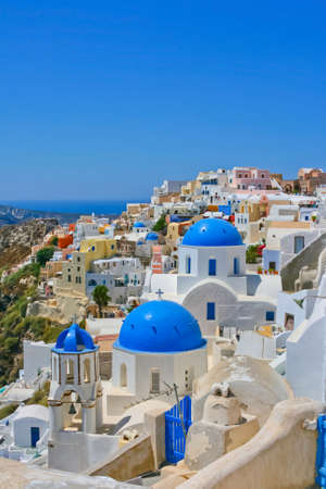 santorini: Magic view of Oia on island of Santorini in Greece. Traditional architecture with famous blue churches. Stock Photo