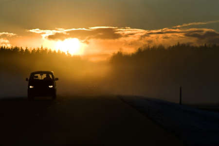 Fog on the road at the start of winter. Bright sun in clouds, minivan on the left side of road and dangerous overtaking in the background. This is E22A10 winter road Riga - Ventspils.