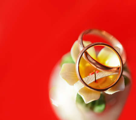 Two golden wedding rings at small beautiful bell with a red copyspace background Stock Photo - 9953742