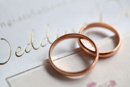 Classic golden rings on the silver wedding card Stock Photo