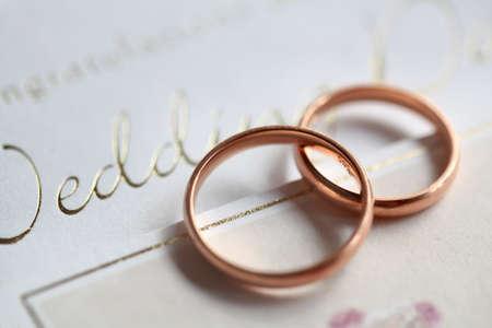 Classic golden rings on the silver wedding card Standard-Bild