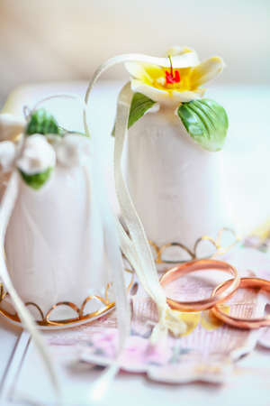 Two gold wedding rings near two small beautiful bells photo