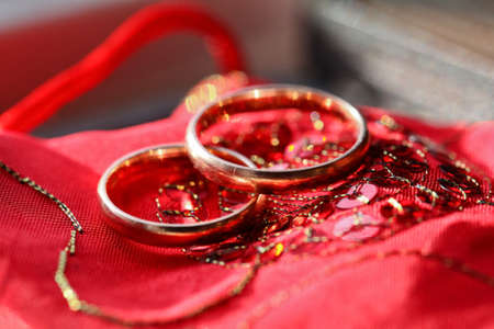 Wedding golden rings on the red silk material background photo