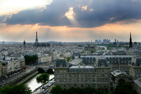 panoramic windows: Classic panorama of Paris in France. View of sunset from Notre Dame de Paris. Eiffel tower in the left side. Skyscrapers and office buildings in a background. Historic buildings in a front on island de la Cite. Stock Photo