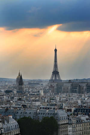 Classic panorama of Paris in France. View of sunset from Notre Dame de Paris. Eiffel tower in the right side. Skyscrapers and office buildings in a background. Historic buildings in a front on island de la Cite. photo