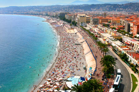Luxury resort of French riviera. Beautiful panorama city of Nice in France. Sunny, summer day. Mediterranean sea, public beach, famous quay, palms and houses of Nice.