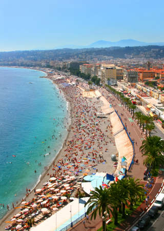 Luxury resort of French riviera. Fantastic panorama city of Nice in France. Sunny, summer day. Mediterranean sea, public beach, famous quay, palms and houses of Nice.