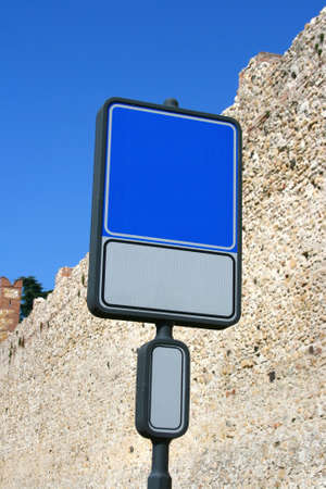 Blank and isolated road sign (blue&white) against brick wall with a place for a picture or text. Clipping path included. photo