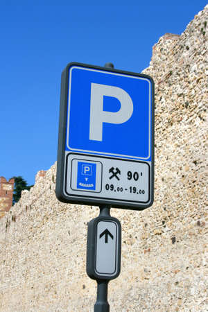 Parking road road sign (blue&white) against brick wall with a time and arrow. Clipping path included. photo