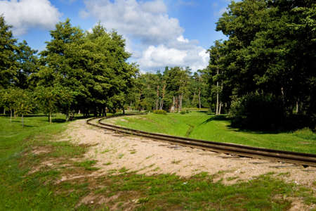 Small railway track in beautiful nature park on a summer day in city of Ventspils, Latvia. This is a clean and green park near the Baltic Sea. Clouds, sun and silence it