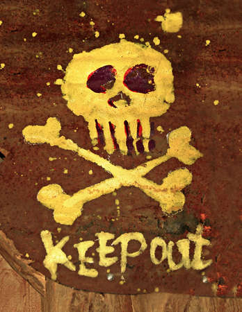 Warning sign Keep out with skull & bones on rusted metal surface. photo