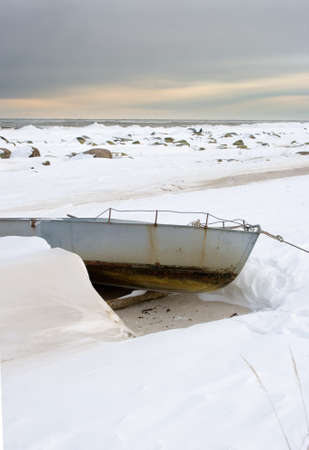 Beautiful winter sunset over the Baltic Sea in Latvia. -15, ice and snow is everywhere. Old abandoned rusty boat in a front. Stock Photo