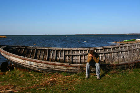 One young sad man sitting on the big lonely old boat near the Baltic Sea on island Saaremaa in Estonia.