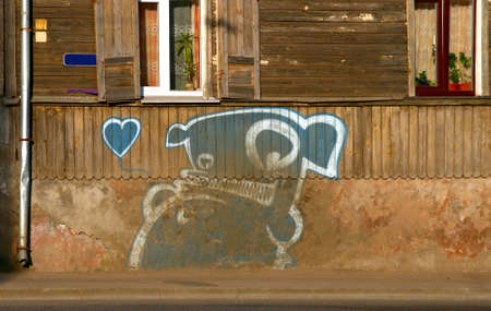 His name is Kiwie and this is a famous urban character in city of Riga in Latvia. Vintage wall and an old house complete the composition. photo