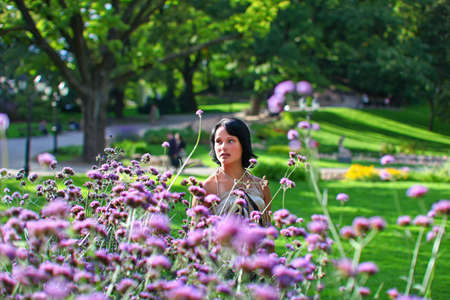 latvia girls: Sweet women is standing near to beautiful bush of violet flowers in Central park at summer day in Riga, Latvia Stock Photo