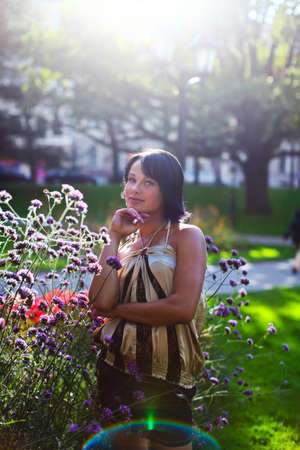 latvia girls: Beautiful model is posing near to bush of violet flowers in Central park at summer day in Riga, Latvia
