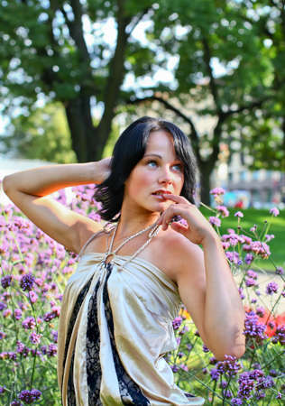 Adorable sexual pose of girl near to beautiful violet flowers in central park at summer day in Riga, Latvia