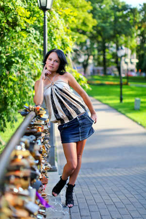 denim skirt: Adorable girl is standing on the bridge with many lock on it. Beautiful summer day in central park of Riga, Latvia