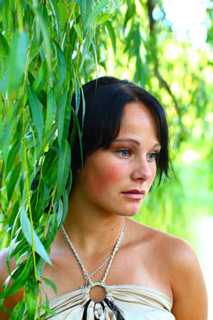 Very sadness young girl is standing in leaves of weeping willow in central park at summer day in Riga, Latvia photo