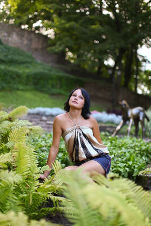 latvia girls: Portrait of young sadness woman which is sitting near to bush of fern in central park against sculpture of horse at Bastion hill in Riga, Latvia