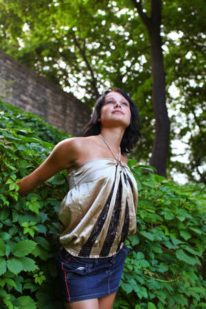 Pretty young woman is dreaming about something in bush of ivy and holds hands in wall of green leafs. Summer day in central park at Bastion hill in Riga, Latvia