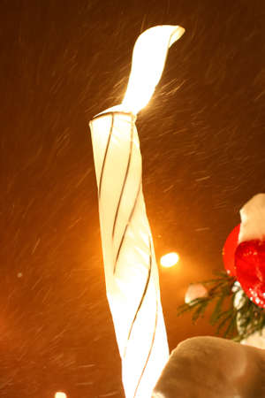 Big burning candle is shining on a christmas tree in the high snow and wind at night photo