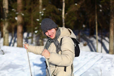 nordic ski: Closeup of young man cross-country skiing on a sunny winter day through the forest