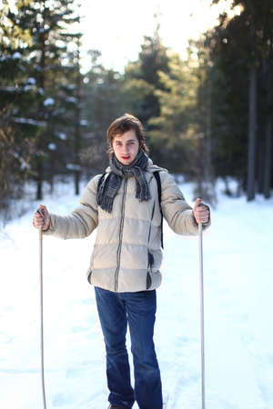 Beautiful young man cross-country skiing on a winter day through the forest photo
