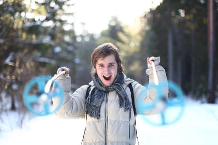 Screaming skier with cross-country poles on sunny winter day in the forest (focus on young man) photo