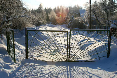 wicket gate: Closed gates at countryside winter road in a village with very high snow