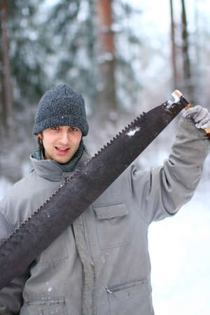 Forest worker is holding big sharp saw in hands on winter day in the snowy forest
