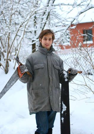 Forest worker is holding two sharp saws and one axe in hands on winter day in the snowy forest photo