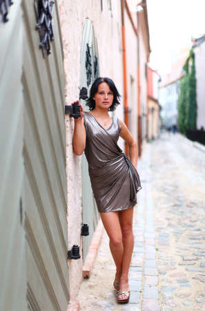 latvia girls: Young girl is standing near to old wooden door at full length on street of Old Riga, Latvia