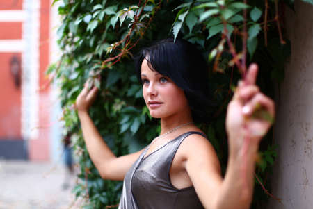 latvia girls: Portrait of a cute girl which is holding ivy at summer day on street of Old Riga, Latvia