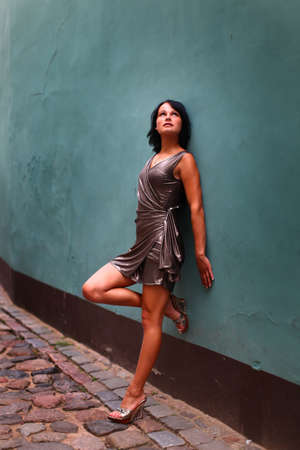 short: Gorgeous woman in beautiful dress is leaning with her back against a wall in sexual and beautiful pose on the street of Old Riga, Latvia