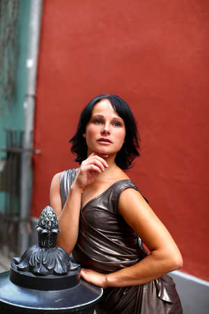 sweet woman in beautiful silver dress is leaning to a sculpture against a grunge vinous wall with pensive look on the street of Old Riga, Latvia photo