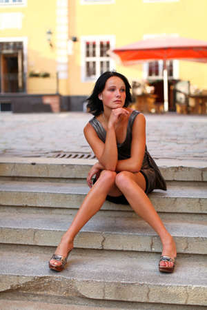 Beautiful brunette is sitting in pose on the steps on the street of Old Riga, Latvia.