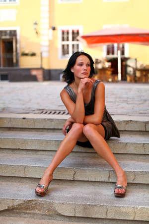 mini jupe: Belle brune est assise dans la pose sur les marches de la rue de la vieille ville de Riga, en Lettonie.
