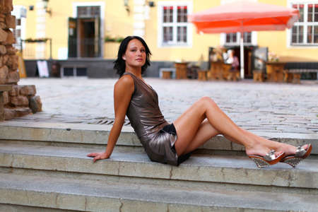 Beautiful brunette is sitting in sexual pose on the steps on the street of Old Riga, Latvia. She is a little bit sad and also dreaming about something against old barracks and cafe at summer day. photo