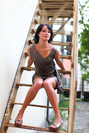 latvia girls: Beautiful brunette is sitting in sexual pose on the steps on the street of Old Riga, Latvia.