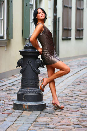 Gorgeous woman in beautiful dress is leaning with her back against old column beautiful pose on the street of Old Riga, Latvia photo