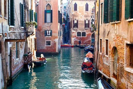 Beautiful colorful canal in Venice with parked gondolas near traditional architecture, Italy