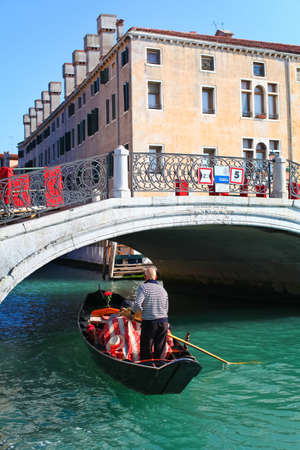 Gondolier with his gondola is going under the bridge of canal in Venice, Italy