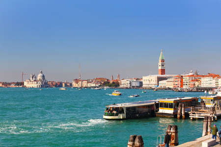 City life on famous Grand Canal in Venice, Italy  Vaporetto station is in front  Basilica di Santa Maria della Salute to the left and Campanile San Marco to the right