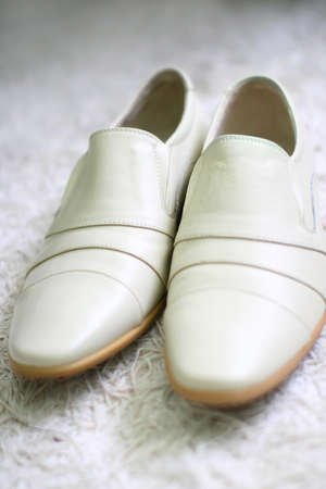 Pair of wedding mens white shoes is lying on a fur carpet and they are ready for a groom. photo