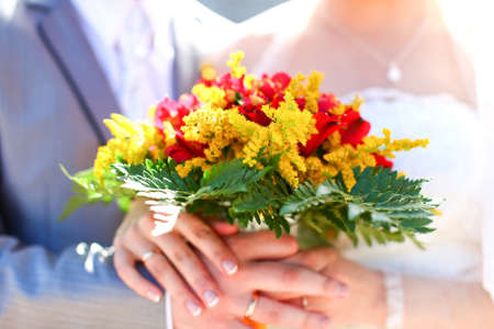 Wonderful wedding bouquet of beautiful colorful flowers which are holding groom and bride together in hands. photo