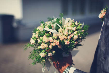 Wonderful wedding bouquet of beautiful roses, which a groom is holding in a hand before bridal ceremony. photo