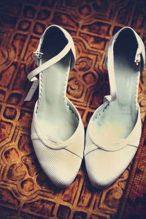 Pair of wedding classic womens white shoes is lying on a carpet and they are ready for a bride. photo